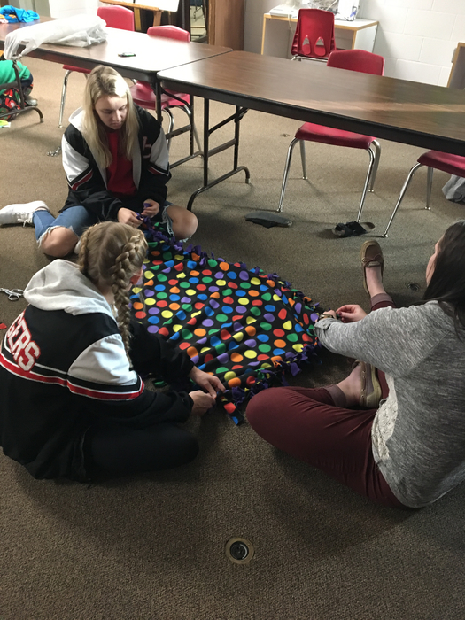 Members making a cuddle blanket.